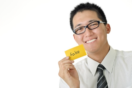 "Professional man holding up word ""fake"" on post it."