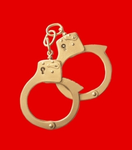 golden handcuffs on red background