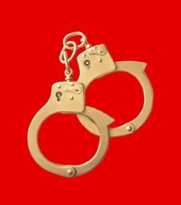 golden handcuffs on red background