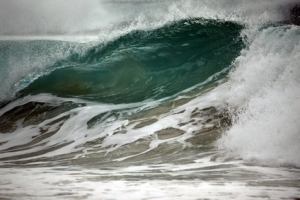 big green wave crashes on shore