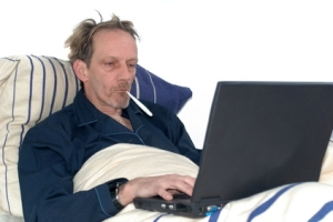 man sick in bed with laptop