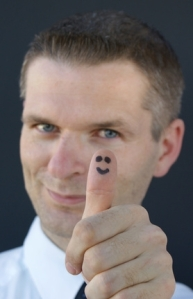 happy face on businessman's thumb