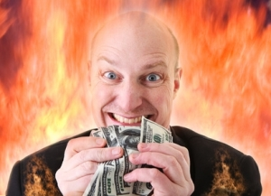 Businessman holding money against background of flames