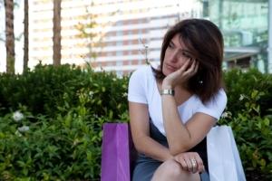 sad shopper sitting in park