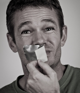 man removing duct tape from mouth