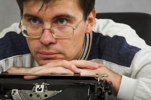 man in glasses with typewriter