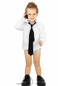 toddler with cell phone in white shirt, tie and large shoes