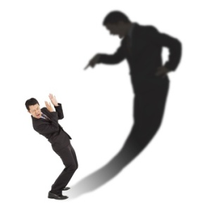 business guy scared by large shadow