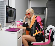 woman in office wearing black leather coat and pink accessories
