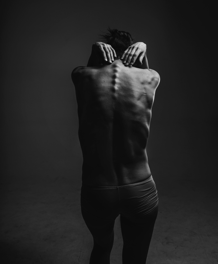 black white photo of thin person standing with back to camera, head down and hands around shoulders