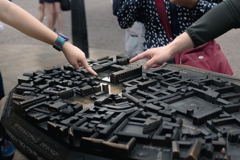 two people pointing at different parts of black model of a campus or city