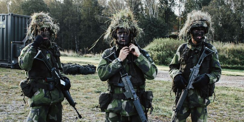 3 soldiers in fatigues with vegetation on heads and blacked out faces
