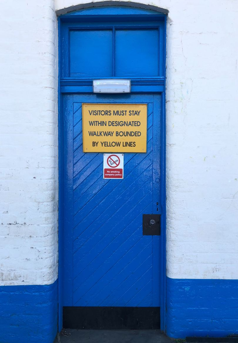 vivid blue door with yellow sign saying Visitors must stay within designated walkway bounded by yellow lines