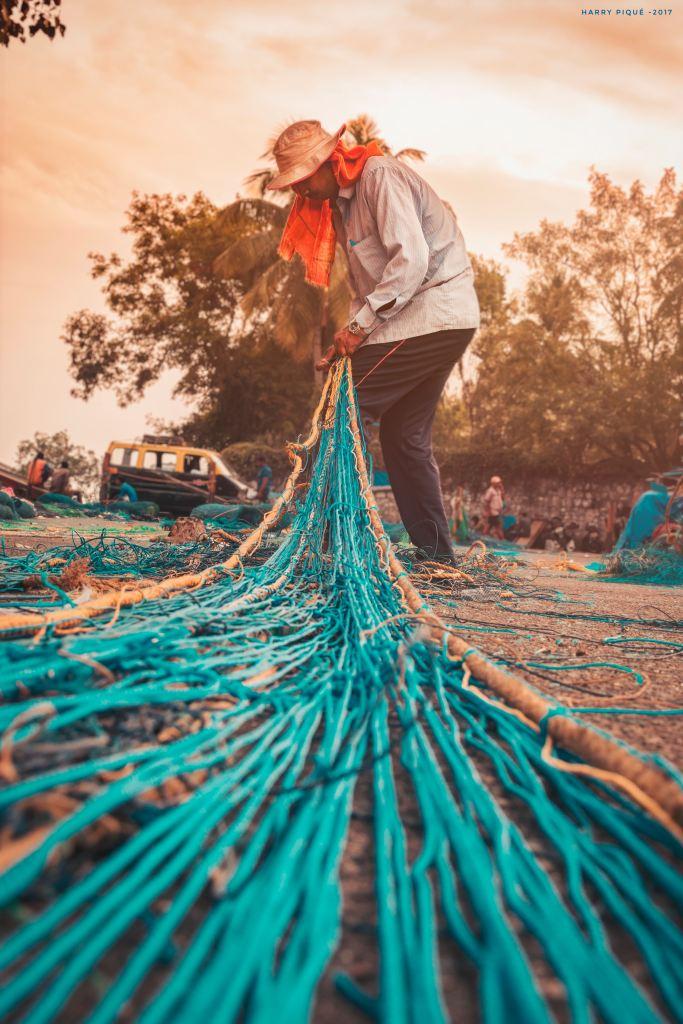 man repairing large blue nets