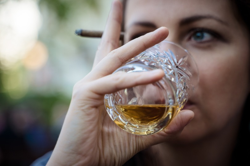 young white woman drinking whiskey from glass and holding cigarette