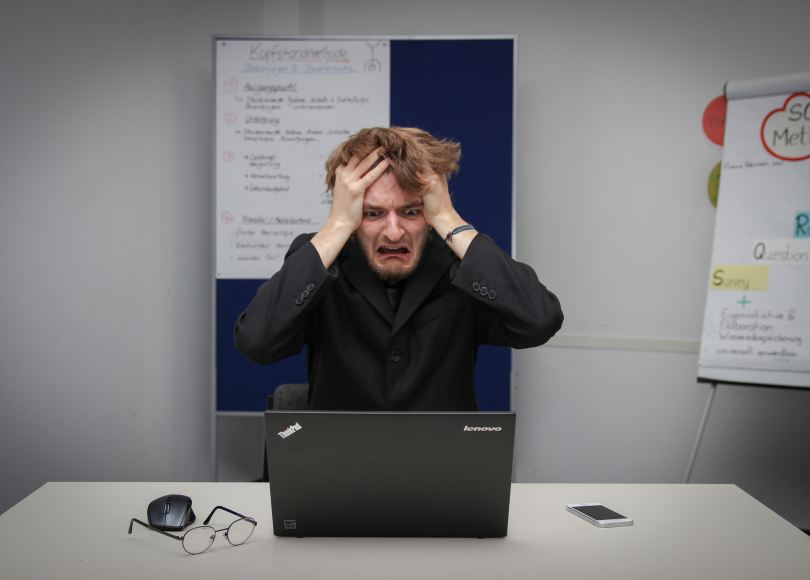 30-something white man in black business clothes with hands to head and upset look on face in front of laptop