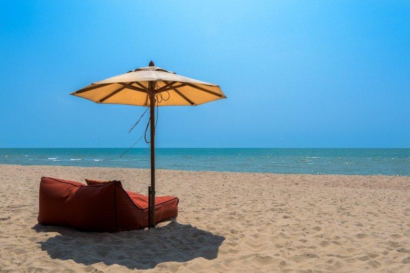 tan beach umbrella over plush brown beach chairs on Thailand beach