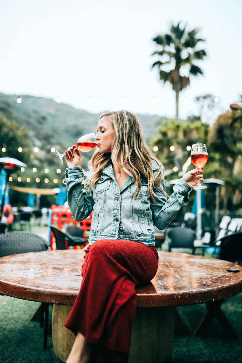young woman in casual clothing sitting on large table, holding one glass of wine while drinking another