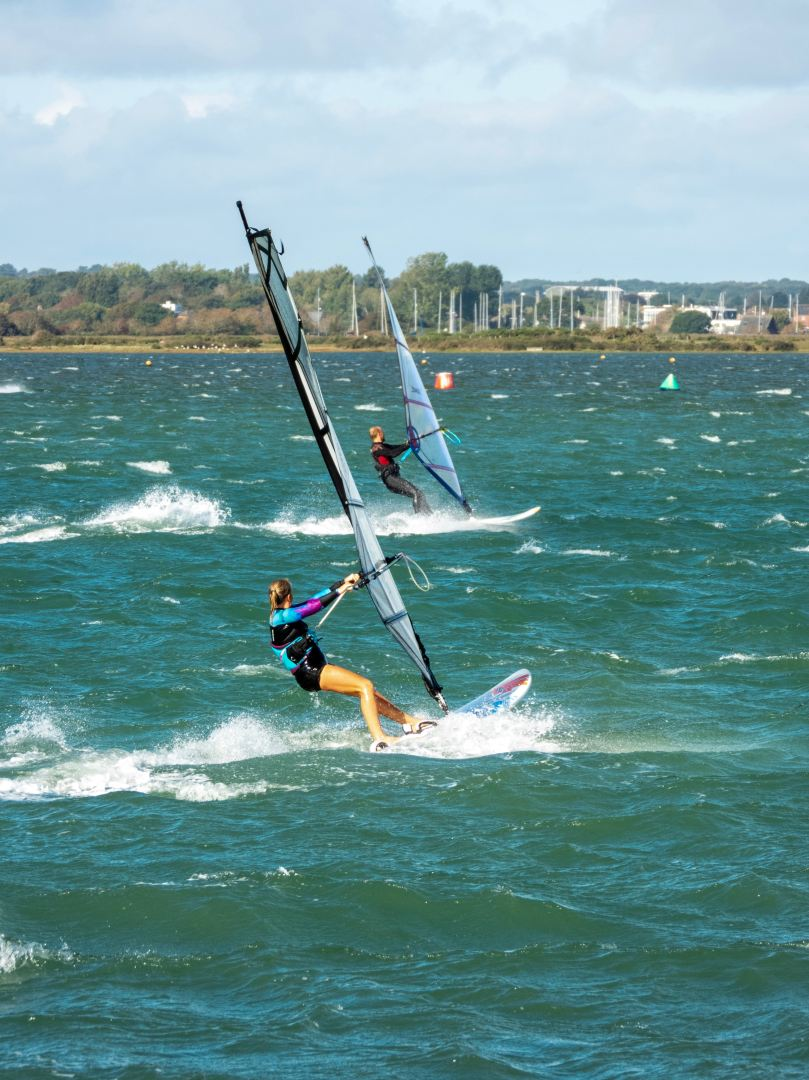 two women windsurfing on bay with city in background