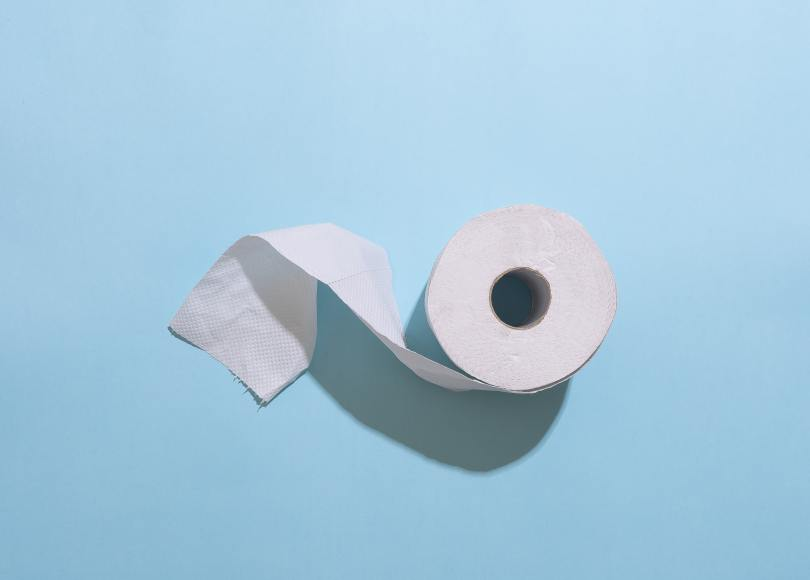 single roll of toilet paper on light blue background